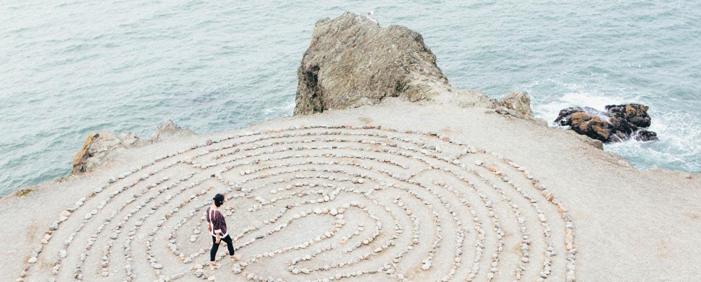 Mujer caminando sobre un laberinto en una playa