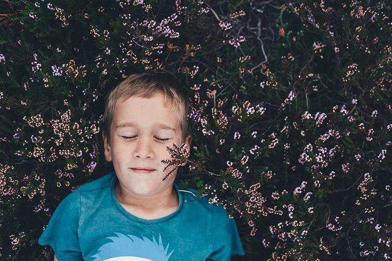 Niño sonrientre meditando en la hierba
