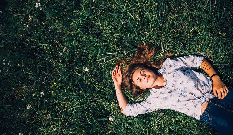 Mujer joven tendida en la hierba
